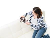 Junger schöner glücklicher aufpassender Ultraschall der schwangeren Frau scannt lizenzfreie stockfotografie