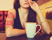 Junger schöner Hippie tätowierte Frau mit dem roten gelockten Haar an der Bar mit Tasse Kaffee Stockfotografie