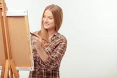 Junger schöner Künstler, der mit einem Zeichnungsgestell aufwirft Lizenzfreies Stockfoto