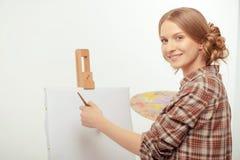 Junger schöner Künstler, der mit einem Zeichnungsgestell aufwirft Stockfotografie