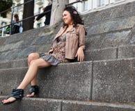 Junger schöner Latina, der auf Treppen sitzt lizenzfreies stockbild