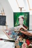 Junger schöner Mädchenmaler in einem weißen Studio zeichnet auf ein Gestell auf Segeltuch stockfoto