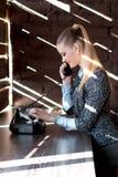 Junger schöner Mädchensekretär, der am Telefon im Büro lächelt und spricht Stockfotografie