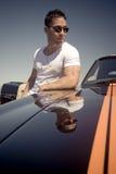 Junger schöner Mann, der am Muskelauto sich lehnt Stockfotografie