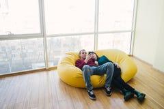 Junger schöner Mann und Mädchen, die in einem Raum mit einem modernen Innenraum stillsteht Sie benutzen einen Handy Lizenzfreies Stockbild