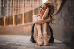 Junger schöner moderner Artballetttänzer, der aus den Grund im schwarzen Kleid sitzt Selektiver Fokus stockfotos