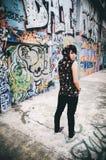 Junger schöner Punk-emo Mantel mit Haubenhintergrundgraffiti Lizenzfreie Stockfotografie