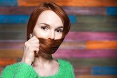 Junger schöner rothaariger Mädchenbedeckungsmund mit ihrem Haar Stockfotografie