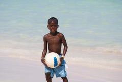 Junger schöner schwarzer Junge in den blauen kurzen Hosen, die Fußball auf dem sonnigen karibischen Strand gleich nach Schwimme lizenzfreie stockfotografie
