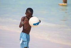 Junger schöner schwarzer Junge in den blauen kurzen Hosen, die Fußball auf dem sonnigen karibischen Strand gleich nach Schwimme lizenzfreies stockfoto
