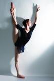 Junger schöner Tänzer, der auf einem Studio aufwirft lizenzfreie stockfotos