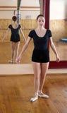 Junger schöner Tänzer, der in der Eignungsmitte auf einem Studio mirr aufwirft Stockfotografie