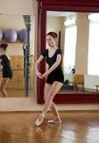 Junger schöner Tänzer, der in der Eignungsmitte auf einem Studio mirr aufwirft Lizenzfreie Stockfotografie