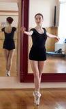 Junger schöner Tänzer, der in der Eignungsmitte auf einem Studio mirr aufwirft Lizenzfreies Stockfoto