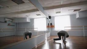 Junger schöner Tänzer, der nahe dem Spiegel im Ballsaal springt und spinnt Mitglied der Tanzgruppe im grauen Pullover ist herein stock video