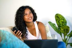 Junger schöner und glücklicher Mischethnie Kaukasier und Schwarzafrikaner Amerikanerin, die zu Hause Couch unter Verwendung des H stockbilder