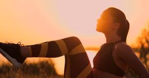 Junger Schönheitsathlet, der auf dem Strand tut Übungen für die Muskeln der ABS bei Sonnenuntergang übt Herein sich verdrehen stock video