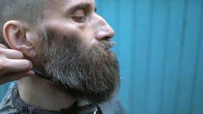 Junger Schönheitsfriseur, der sorgfältig Bart des merkwürdigen Hippie-Mannes von mittlerem Alter in experimentellem im Freien tri stock video footage