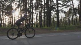 Junger sch?ner M?dchenradfahrer reitet Fahrrad im Teil Folgen Sie Schuss mit Sonne durch B?ume auf dem Hintergrund Radfahrenkonze