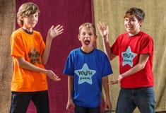 Junger Schauspieler schreit neben zwei Freunden Stockfoto