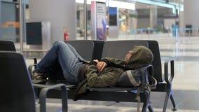 Junger schlafender Mann des Passagiers bei der Aufwartung des Flugzeugs am Flughafenfluggastterminal stock video footage