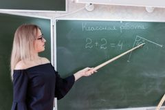 Junger schlanker schöner blonder Lehrer in einem schwarzen Kleid Stockfotografie