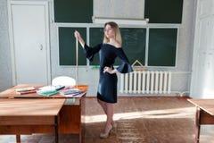 Junger schlanker schöner blonder Lehrer in einem schwarzen Kleid Stockbilder