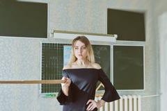 Junger schlanker schöner blonder Lehrer in einem schwarzen Kleid Lizenzfreie Stockbilder