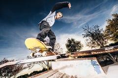 Junger Schlittschuhläufer, der ein Schleifen auf Skatepark während des Sonnenuntergangs macht lizenzfreies stockfoto