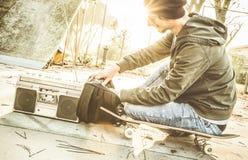 Junger Schlittschuhläufer, der Musik vom Rucksack am skatepark spielt Stockfotos