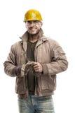 Junger schmutziger Arbeitskraft-Mann mit dem Schutzhelmsturzhelm, der ein Arbeit glo hält Lizenzfreies Stockbild