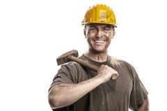 Junger schmutziger Arbeitskraft-Mann mit dem Schutzhelmsturzhelm, der einen Hammer hält stockfoto
