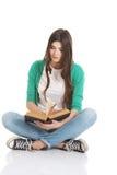 Junger schöner Student, der mit Buch, Lesung, lernend sitzt. Lizenzfreie Stockbilder