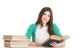 Junger schöner Student, der mit Buch, Lesung, lernend sitzt. Stockfoto