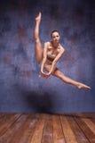 Junger schöner Tänzer im beige Badebekleidungstanzen Lizenzfreies Stockfoto