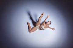 Junger schöner Tänzer im beige Badebekleidungstanzen Stockbild