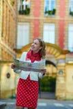 Junger schöner weiblicher Tourist mit Karte in Paris Stockfoto