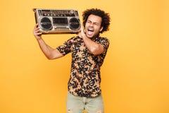 Junger schreiender afrikanischer Mann, der mit Tonbandgerät steht Lizenzfreie Stockfotografie