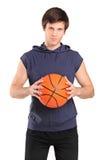 Junger Schulejunge, der einen Basketball anhält Stockbild