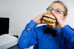 Junger Schulejunge, der Hamburger isst stockfotos
