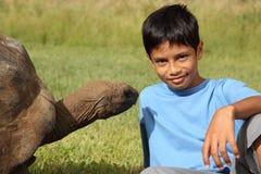 Junger Schulejunge, der neben riesiger Schildkröte sitzt Lizenzfreie Stockbilder