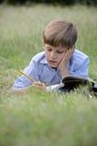 Junger Schuljunge, der die Hausarbeit allein, liegend auf Gras tut Lizenzfreie Stockfotografie