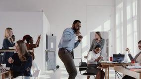 Junger schwarzer Chefgeschäftsmann des roten epischen glücklichen Spaßes, der epischen Tanz im Büro feiert Erfolg mit Teamzeitlup stock video footage