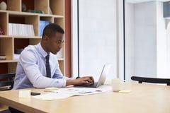 Junger schwarzer Geschäftsmann, der allein oben in einem Büro, Abschluss arbeitet lizenzfreies stockfoto