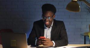 Junger schwarzer Geschäftsmann, der nette Leselustige Textnachrichten unter Verwendung des Smartphone im Nachtbüro lacht stock footage