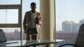 Junger schwarzer Geschäftsmann im Anzug unter Verwendung des bereitstehenden Fensters des Smartphone im Büro in der Sonne stock video
