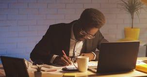 Junger schwarzer Geschäftsmann mit der Laptop-Computer und Papieren, die im Nachtbüro arbeiten Er unterzeichnet die Dokumente Ges stock video footage