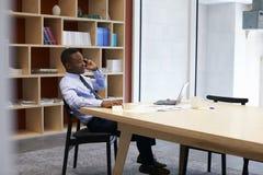 Junger schwarzer Geschäftsmann unter Verwendung des Smartphone im Sitzungssaal stockfotografie