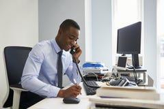 Junger schwarzer Geschäftsmann unter Verwendung des Telefons an seinem Schreibtisch lizenzfreie stockbilder