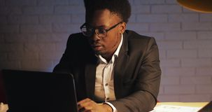 Junger schwarzer Gesch?ftsmann mit der Laptop-Computer und Papieren, die im Nachtb?ro arbeiten Er unterzeichnet die Dokumente Ges stock footage